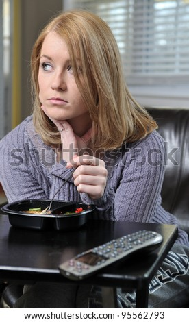 Beautiful blonde woman sitting in chair in pastel sweater eating a frozen (TV) dinner - sad looking off in distance - stock photo