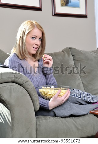 Beautiful blonde woman sitting on couch in pastel sweater and sweats holding a bowl of popcorn - home entertainment - stock photo