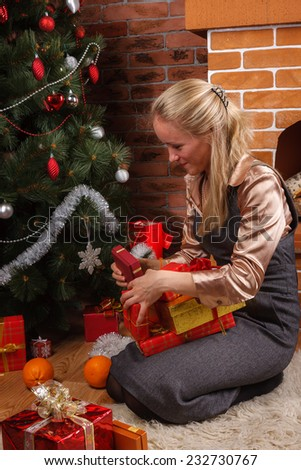 Beautiful blonde woman sorting through the presents under the Christmas tree - stock photo