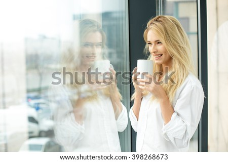 Beautiful blonde woman standing next to a window, wearing men shirt and drinking coffee - stock photo