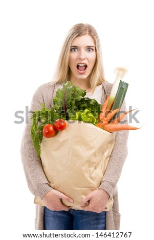 Beautiful blonde woman tired of carrying a bag full of vegetables, isolated over white background - stock photo