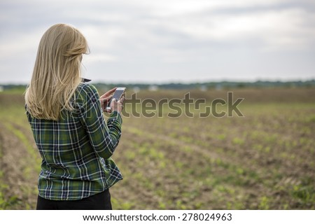 Beautiful blonde woman using mobile smart phone in the middle of nowhere - stock photo