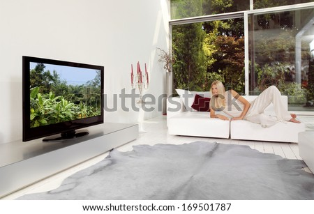 beautiful blonde woman watching TV at home - stock photo