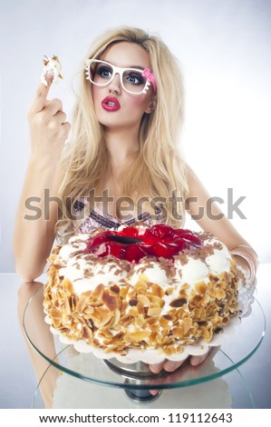 Beautiful blonde woman with a cake. Sweet sexy lady with glasses. - stock photo