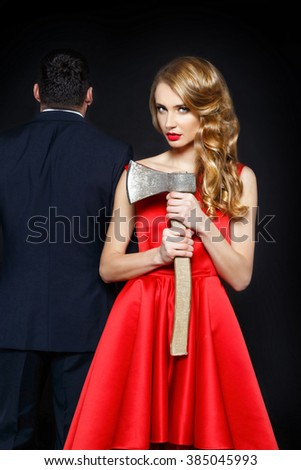 Beautiful blonde woman with ax near the man in suit.  The concept of treason, a family quarrel, murder - stock photo