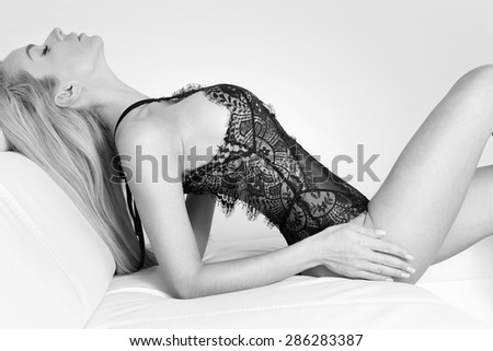 Beautiful blonde woman with blond long hair on blue-green eyes lying on her back on the couch white in sexy positions - stock photo