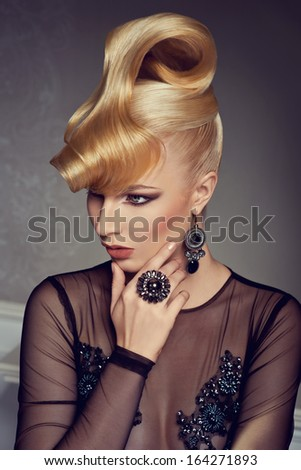 beautiful blonde woman with creative hairstyle wearing gorgeous evening dress  - stock photo