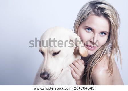 beautiful blonde woman with her dog, studio shot. horizontal - stock photo