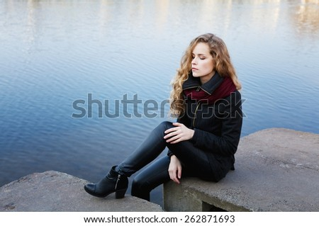 beautiful blonde woman with long curly hair sitting on the banks of the blue river water having closed eyes and enjoying silence, meditation or relaxation concept  - stock photo