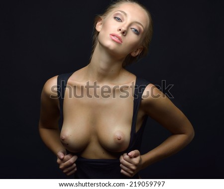 Beautiful blonde woman with naked breast in a black underwear posing in a dark Studio. Torso portrait. - stock photo