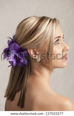 Beautiful blonde woman with purple flower hair clip - stock photo