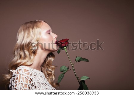 Beautiful Blonde Young Model With Bright Makeup And With a Rose,Curly Hair,White Dress - stock photo