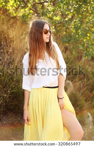 Beautiful blonde young woman in skirt and sunglasses. Female model wearing fashionable clothes and walking on the street - stock photo