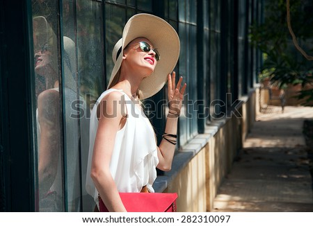 Beautiful blonde young woman posing in garden. Sunny summer day. - stock photo