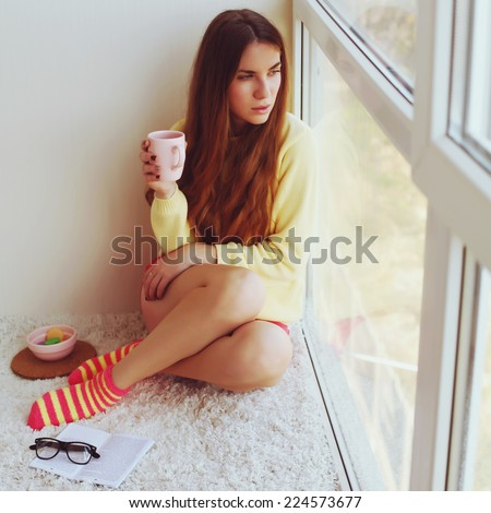 Beautiful blonde young woman sitting on the carpet and drinking morning coffee at the window. - stock photo