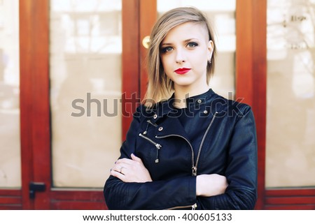 Beautiful blonde young woman wearing fashionable clothes, black leather jacket walking on the street. Fashion photo, street style, red lips. Short blonde hairstyle.  - stock photo