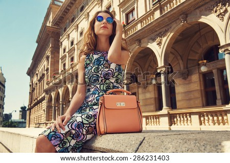 Beautiful blonde young woman wearing fashionable clothes, handbag, sunglasses sitting down in the city. Fashion photo - stock photo