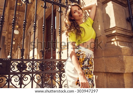 Beautiful blonde young woman wearing fashionable clothes, wonderful hair posing in the city. Fashion photo - stock photo