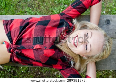 beautiful blonde young woman with her eyes closed sleeping and smiling on a bench in a park or on the woods because she is happy and dreaming happily - stock photo