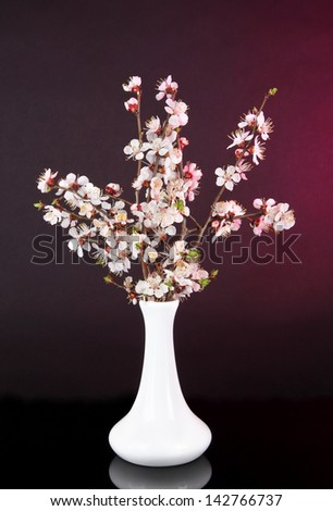 Beautiful blooming branches in vase on bright background - stock photo