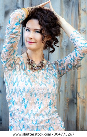 Beautiful blue-eyed brunette on old wooden background - stock photo