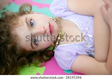 Beautiful blue eyes little girl lying on the floor - stock photo