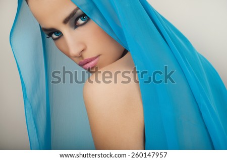 beautiful blue eyes woman with seductive makeup and blue veil over her head, studio white - stock photo