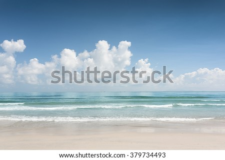 Beautiful blue ocean and scenic tropical white sand beach on sunny summer day. Amazing sea view with azure crystal water. Cloudy sky in background. - stock photo