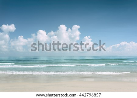 Beautiful blue ocean and scenic tropical white sand beach on sunny summer day. Amazing sea view with azure crystal water. Cloudy sky in background. Toned image. - stock photo