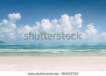 Beautiful blue ocean and tropical white sand beach on sunny summer day. Amazing sea view with azure crystal water. Scenic cloudy sky in background. Toned image. - stock photo