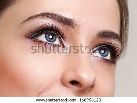 Beautiful blue woman eyes with long lashes looking - stock photo