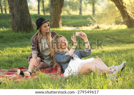 Beautiful bohemian girls relaxing in the park and using a smart phone. - stock photo