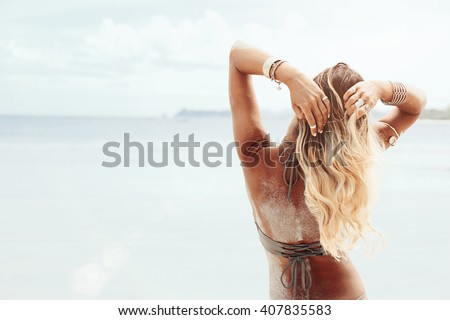 Beautiful bohemian styled and tanned girl at the beach in sunlight - stock photo