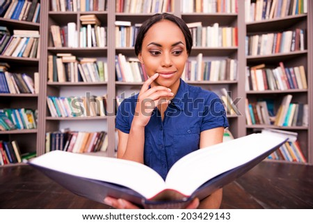 Beautiful bookworm. Thoughtful African female student reading book and holding hand on chin while sitting on the floor in library - stock photo