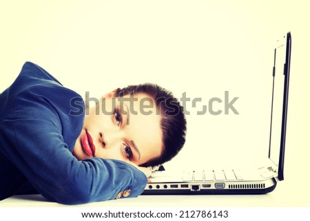 Beautiful bored and tired businesswoman lying down on desk next her laptop - stock photo