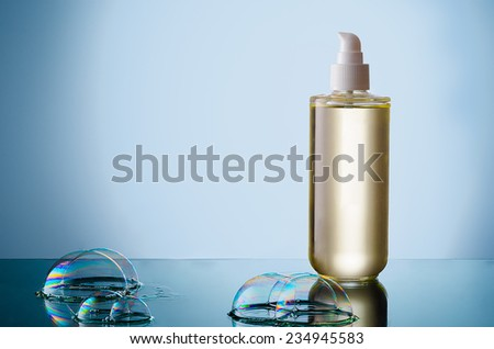 Beautiful bottle of liquid cleanser with soap bubble on a reflective surface. - stock photo