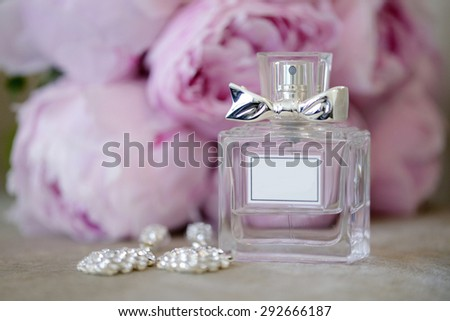 Beautiful bouquet and perfume bottle for bride and groom. Beauty of wedding accessories indoors. Close-up bridal bunch of florets and perfumery. Female and male decoration. Colorful flowers for woman - stock photo