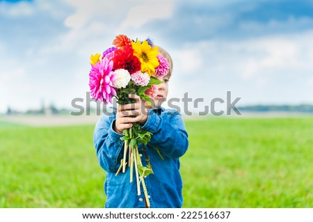 Beautiful bouquet of bright and colorful flowers holding by cute toddler boy - stock photo