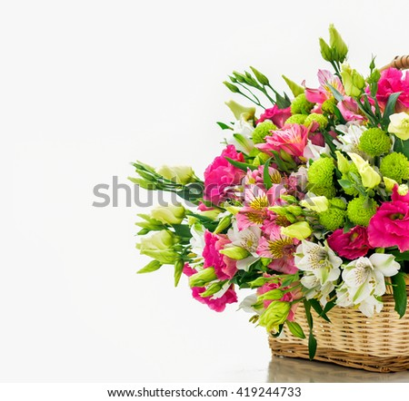 Beautiful bouquet of bright flowers in basket . Isolated on white. - stock photo