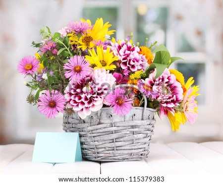 beautiful bouquet of bright flowers in basket on wooden table - stock photo