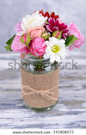 Beautiful bouquet of bright flowers in jar on table on grey background - stock photo