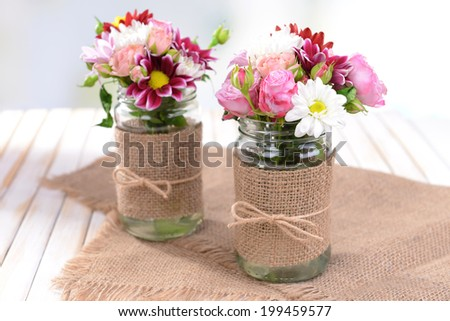 Beautiful bouquet of bright flowers in jars on table on light background - stock photo