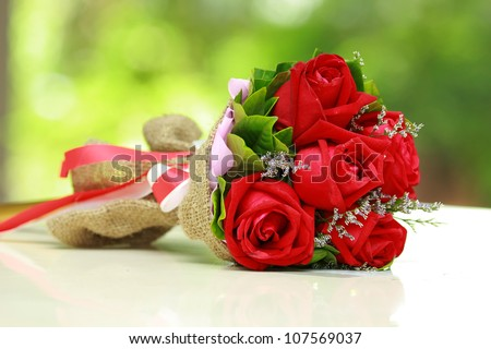 beautiful bouquet of bright red flowers, on  table on green background - stock photo