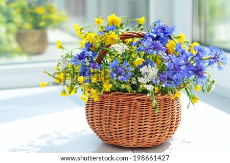 Beautiful bouquet of cornflowers and chamomiles in basket   - stock photo