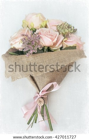 Beautiful bouquet of delicate pink roses on a light background.Floral gift for a wedding or birthday. - stock photo