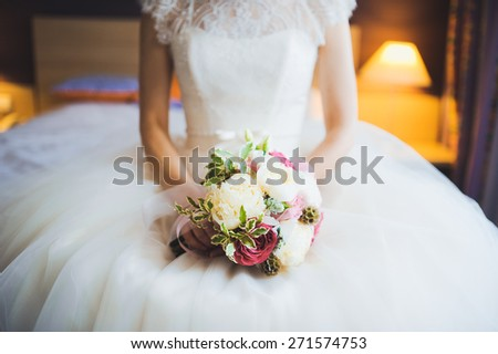 beautiful bouquet of different colors in the hands of the bride in a white dress - stock photo