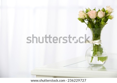 Beautiful bouquet of flowers in vase on window background - stock photo