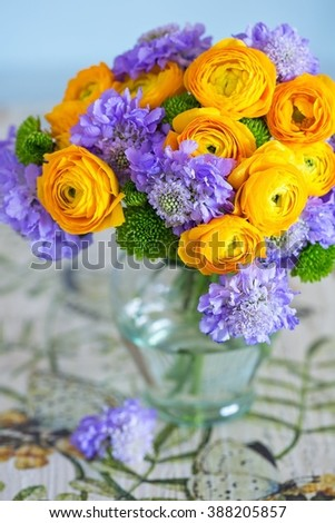 Beautiful bouquet of flowers.Yellow ranunculus flowers close-up in a glass vase on the table. - stock photo