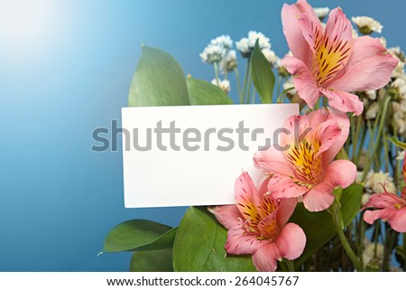 beautiful bouquet of lilies and the card against the blue sky and the sun. - stock photo