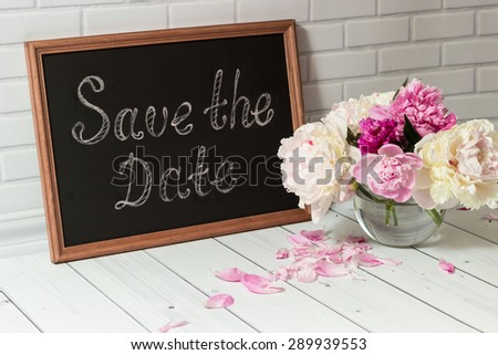 Beautiful bouquet of pink and white peonies in the glass vase with petals on the light grey brick and wood background. - stock photo